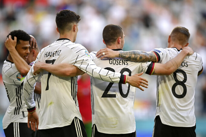 Germany's Robin Gosens celebrates with Kai Havertz and Toni Kroos, right, after scoring his side's fourth goal during the Euro 2020 soccer championship group F match between Portugal and Germany at the Football Arena stadium in Munich, Germany, Saturday, June 19, 2021. (Philipp Guelland/Pool via AP)