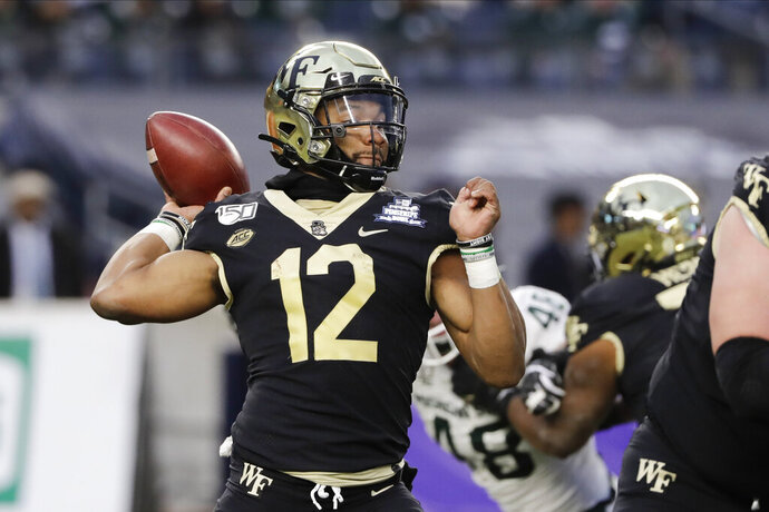 "File-Wake Forest's Jamie Newman (12) throws a pass during the first half of the Pinstripe Bowl NCAA college football game against Michigan State, Friday, Dec. 27, 2019, in New York.  Newman, the Wake Forest transfer who was the projected starting quarterback for No. 4 Georgia, is opting out of the 2020 season to prepare for the 2021 NFL draft. Newman announced his decision on his Twitter account on Wednesday, Sept. 2, 2020. He said he made the decision to skip the season ""after much prayer and discussion with my family.""(AP Photo/Frank Franklin II, File)"