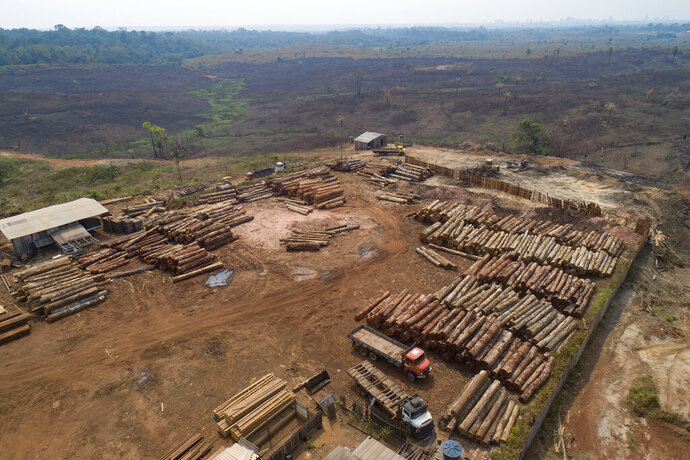 FILE - In this Sept. 2, 2019 file photo, logs are stacked at a lumber mill surrounded by recently charred and deforested fields near Porto Velho, Rondonia state, Brazil. Dozens of Brazilian corporations are calling for a crackdown on illegal logging in the Amazon rainforest, expressing their concerns in a letter Tuesday, July 7, 2020, to the vice president, who heads the government's council on that region. (AP Photo/Andre Penner, File)