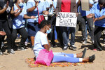 Nurses take part in a protest at a government hospital in Harare, Monday, July, 6, 2020. Thousands of nurses working in public hospitals stopped reporting for work in mid-June, part of frequent work stoppages by health workers who earn less than $50 a month and allege they are forced to work without adequate protective equipment. On Monday, dozens of nurses wearing masks and their white and blue uniforms gathered for protests at some of the country's biggest hospitals in the capital, Harare, and the second-largest city of Bulawayo.(AP Photo/Tsvangirayi Mukwazhi)