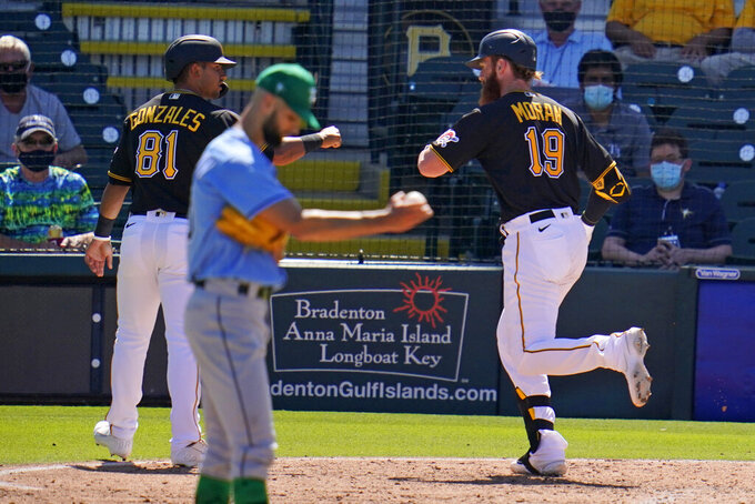 Pittsburgh Pirates' Colin Moran (19) celebrates with Nick Gonzalez (81) after hitting a two-run home run off Tampa Bay Rays pitcher Nick Anderson, center, during the fifth inning of a spring training exhibition baseball game in Bradenton, Fla., Wednesday, March 17, 2021. (AP Photo/Gene J. Puskar)