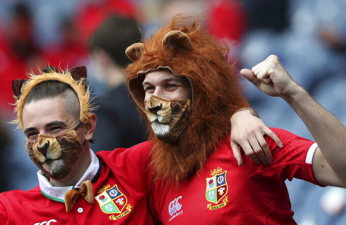 British and Irish Lions' fans pose for photographers before the start of the friendly rugby match between British and Irish Lions and Japan at the Murrayfield stadium in Edinburgh, Scotland, Saturday, June 26, 2021. (AP Photo/Scott Heppell)