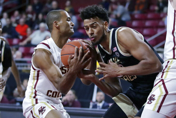 Boston College forward Steffon Mitchell, right, rips the ball out of the hands of Wake Forest center Olivier Sarr, right, during the first half of an NCAA college basketball game in Boston, Wednesday, Nov. 6, 2019. (AP Photo/Charles Krupa)