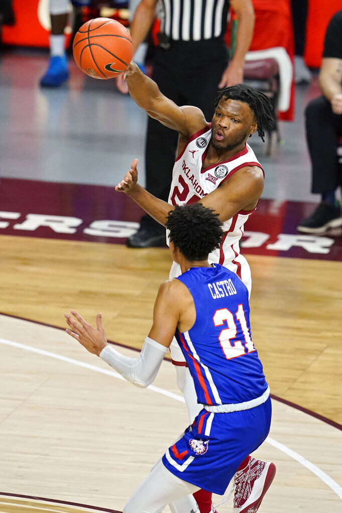 Oklahoma guard Elijah Harkless, top, passes over Houston Baptist guard Pedro Castro (21) in the first half of an NCAA college basketball game Saturday, Dec. 19, 2020, in Norman, Okla. (AP Photo/Sue Ogrocki)