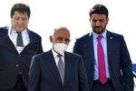 Afghan President Ashraf Ghani, center, flanked by his bodyguard and an official steps down from a plane upon his arrival at Tashkent International airport, Uzbekistan, Thursday, July 15, 2021. Uzbekistan's President Shavkat Mirziyoyev, Afghan President Ashraf Ghani and Pakistan's Prime Minister Imran Khan are among those expected to attend the conference along with foreign ministers of Central and South Asian nations, according to Mirziyoyev's official website. (AP Photo)