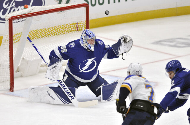 Tampa Bay Lightning goalie Andrei Vasilevskly (88) deflects a shot by St. Louis Blues' Oskar Sundqvist (70) during the period of an NHL hockey game Wednesday, Nov. 27, 2019, in Tampa, Fla. (AP Photo/Steve Nesius)
