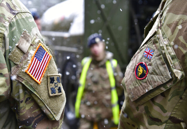 A British and an United States soldier stand side by side after a press conference on the military exercise 'Defender 2020' in Brueck, Germany, Wednesday, Feb. 26, 2020. The exercise with 37000 participants from a total of 18 nations will take place in Europe between January and about June 2020. (Soeren Stache/dpa via AP)