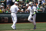Oakland Athletics' Mark Canha, right, is congratulated by third base coach Matt Williams after hitting a solo home run against the San Francisco Giants during the fourth inning of a baseball game in Oakland, Calif., Sunday, Aug. 25, 2019. (AP Photo/Jeff Chiu)