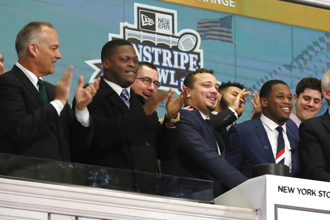 University of Wisconsin football Team Captain Alec Ingold, second from right, and University of Miami football Team Captain Jaquan Johnson, right, ring the New York Stock Exchange opening bell, Wednesday, Dec. 26, 2018. Their teams will play each other in the New Era Pinstripe Bowl, which will be played at New York's Yankee Stadium on Thursday, Dec. 27, 2018. (AP Photo/Richard Drew)