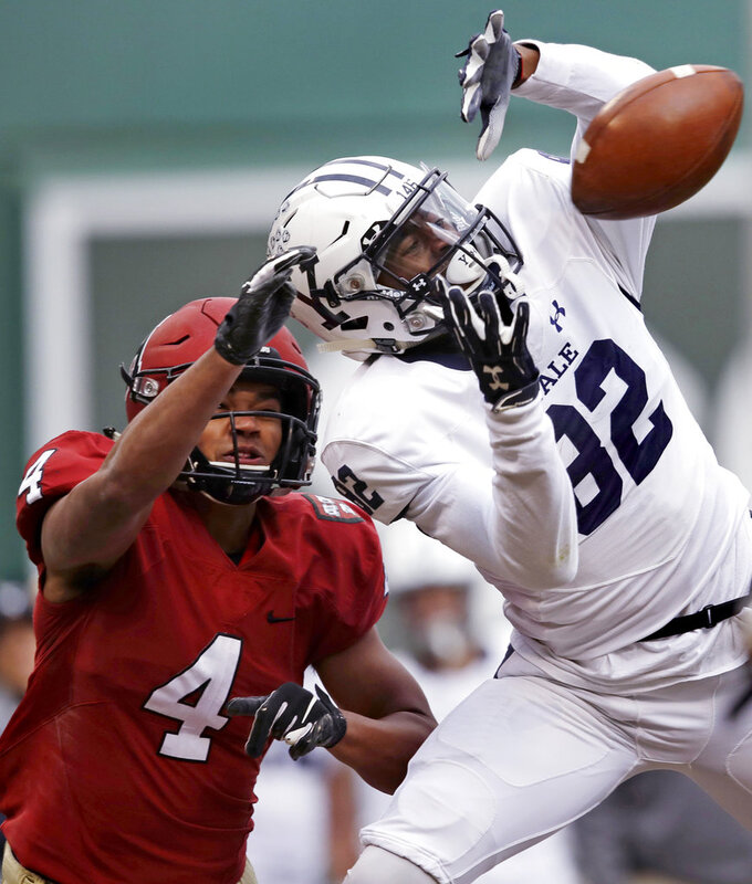 Yale wide receiver Jaylan Sandifer (82) reaches up for a pass against Harvard defensive back Max Jones (4) during the first half an NCAA college football game at Fenway Park in Boston, Saturday, Nov. 17, 2018. Jones was charged with pass interference on the play. (AP Photo/Charles Krupa)