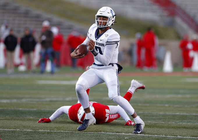 Utah State quarterback Jordan Love (10) runs for yardage after avoiding the tackle by New Mexico defensive lineman Joey Noble (98) during the second half of an NCAA college football game on Saturday, Nov. 30, 2019 in Albuquerque, N.M. (AP Photo/Andres Leighton)