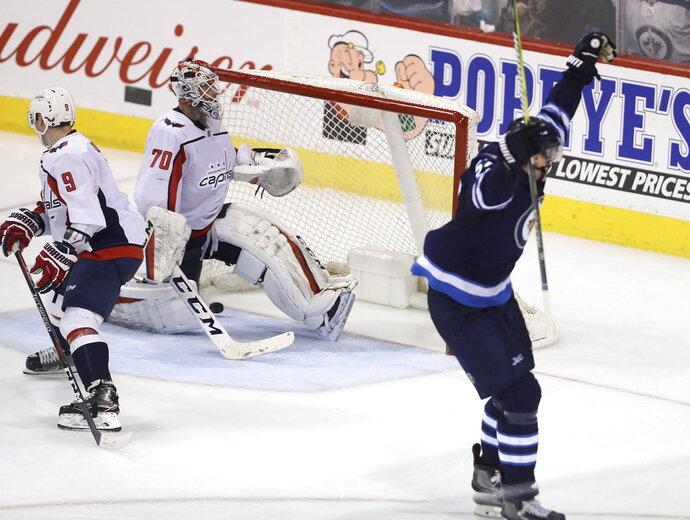 Winnipeg Jets' Tyler Myers (57) celebrates his overtime goal on Washington Capitals goaltender Braden Holtby (70) in an NHL hockey game Tuesday, Feb. 13, 2018, in Winnipeg, Manitoba. (Trevor Hagan/The Canadian Press via AP)