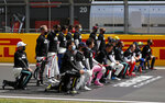 Drivers wearing a Black Lives Matter shirt, takes a knee and stand against racism in the pit lane prior the British Formula One Grand Prix at the Silverstone racetrack, Silverstone, England, Sunday, Aug. 2, 2020. (AP Photo/Frank Augstein, Pool)