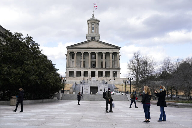 People walk across the quiet Legislative Plaza in front of the State Capitol Sunday, Jan. 17, 2021, in Nashville, Tenn. The FBI warned of the potential for armed protests at the nation's Capitol and all 50 state capitol buildings beginning this weekend. (AP Photo/Mark Humphrey)