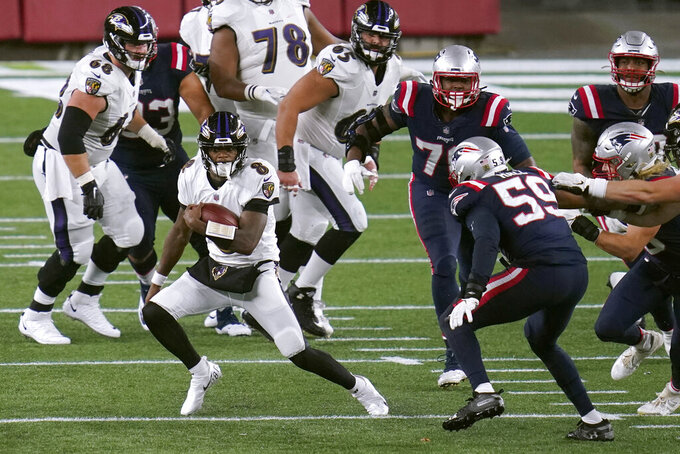 Baltimore Ravens quarterback Lamar Jackson, left, scrambles away from New England Patriots linebacker Terez Hall (59) in the first half of an NFL football game, Sunday, Nov. 15, 2020, in Foxborough, Mass. (AP Photo/Charles Krupa)