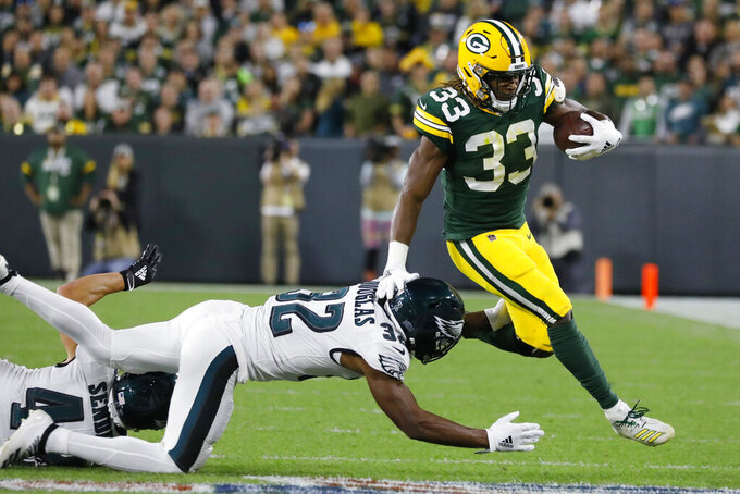 Green Bay Packers running back Aaron Jones breaks the tackle of Philadelphia Eagles cornerback Rasul Douglas during the first half of an NFL football game Thursday, Sept. 26, 2019, in Green Bay, Wis. (AP Photo/Jeffrey Phelps)