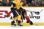 Nashville Predators defenseman Dan Hamhuis (5) checks Calgary Flames left wing Matthew Tkachuk (19) during the first period of an NHL hockey game Thursday, Oct. 31, 2019, in Nashville, Tenn. (AP Photo/Mark Zaleski)