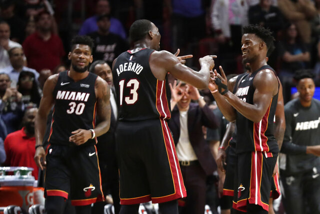 Miami Heat center Bam Adebayo (13) and forward Jimmy Butler (22) react during overtime of an NBA basketball game against the Atlanta Hawks, Tuesday, Dec. 10, 2019, in Miami. The Heat won 135-121 in overtime. (AP Photo/Lynne Sladky)