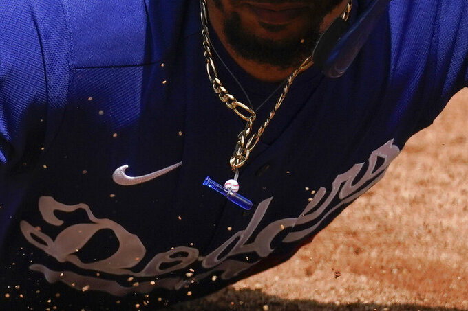 A small baseball and bat are shown hanging from a chain worn by Los Angeles Dodgers' Mookie Betts as he slides safely back to first base during the second inning of a spring training baseball game against the Colorado Rockies Monday, March 15, 2021, in Scottdale, Ariz. (AP Photo/Ashley Landis)