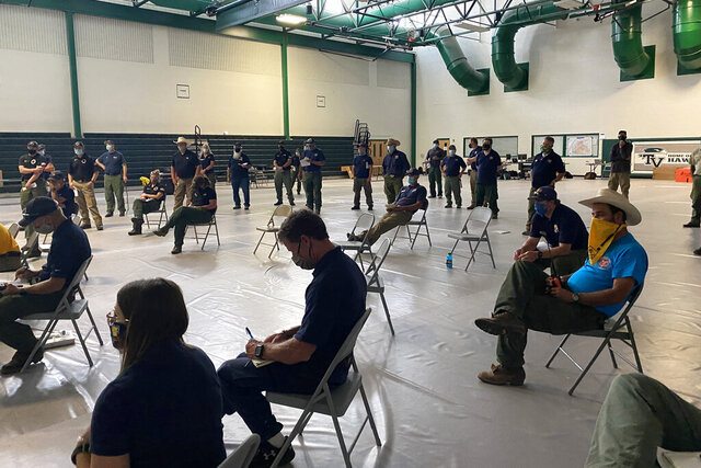 In this July 2020, photo provided by the U.S. Forest Service, wildland firefighters attend a socially distanced briefing at the Smokejumper Depot in Missoula, Mont., before the wildfire season begins. To protect crews from COVID-19 exposure, incident commanders are taking precautions to keep infection risk at a minimum. (U.S. Forest Service via AP)