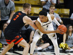 Colorado guard Tyler Bey, right, looks to pass the ball as Oregon State forward Tres Tinkle defends in the first half of an NCAA college basketball game Sunday, Jan. 5, 2020, in Boulder, Colo. (AP Photo/David Zalubowski)