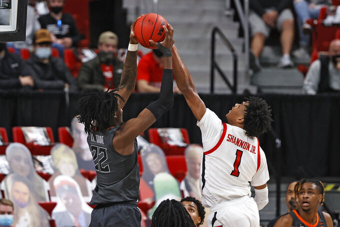 Oklahoma State's Kalib Boone (22) rebounds away from Texas Tech's Terrence Shannon Jr. (1) during the first half of an NCAA college basketball game Saturday, Jan. 2, 2021, in Lubbock, Texas. (AP Photo/Brad Tollefson)