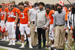 Oklahoma State running back Chuba Hubbard, center, watches from the sidelines wearing a boot on his right foot during an NCAA college football game against Texas Tech in Stillwater, Okla., Saturday, Nov. 28, 2020. From the left are Braden Cassity (90), Spencer Sanders (3), Hubbard, LD Brown (0), and head coach Mike Gundy. (AP Photo/Sue Ogrocki)