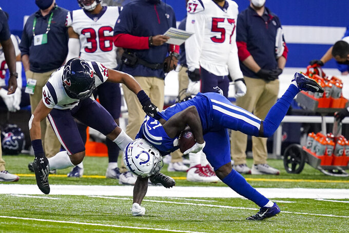 Indianapolis Colts wide receiver Zach Pascal (14) is tackled by Houston Texans cornerback Vernon Hargreaves III (26) in the first half of an NFL football game in Indianapolis, Sunday, Dec. 20, 2020. (AP Photo/Darron Cummings)