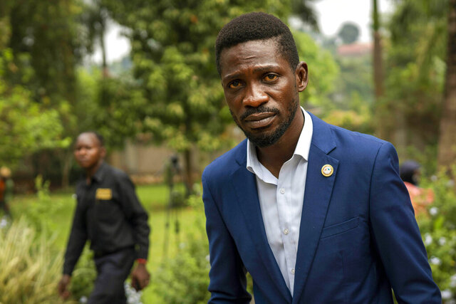 FILE- in this Jan. 15, 2021 file photo, Uganda's leading opposition challenger Bobi Wine walks back to his residence after giving a press conference outside Kampala, Uganda. Despite failing to dislodge the long-time leader President Yoweri Museveni, Wine has emerged from Jan. 14, 2021 disputed polls as the country's most powerful opposition leader after his party won the most seats of any opposition group in the national assembly. (AP Photo/Jerome Delay, File)