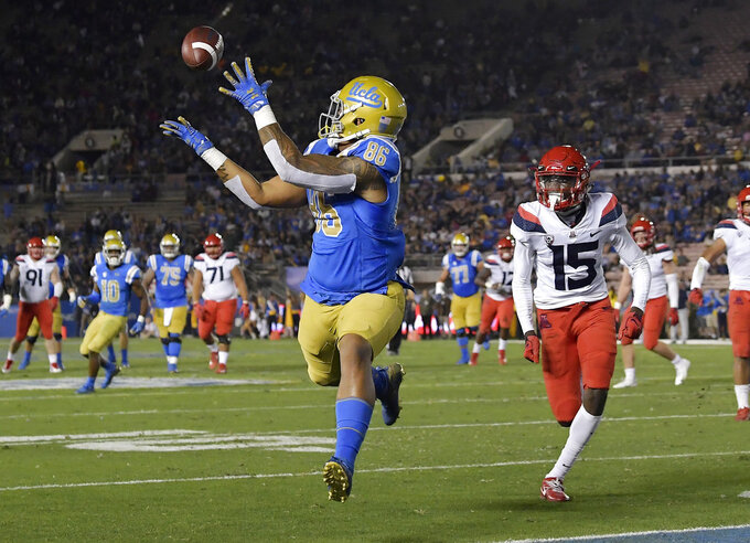 UCLA tight end Devin Asiasi, left, makes a touchdown catch as Arizona cornerback McKenzie Barnes watches during the first half of an NCAA college football game, Saturday, Oct. 20, 2018, in Pasadena, Calif. (AP Photo/Mark J. Terrill)