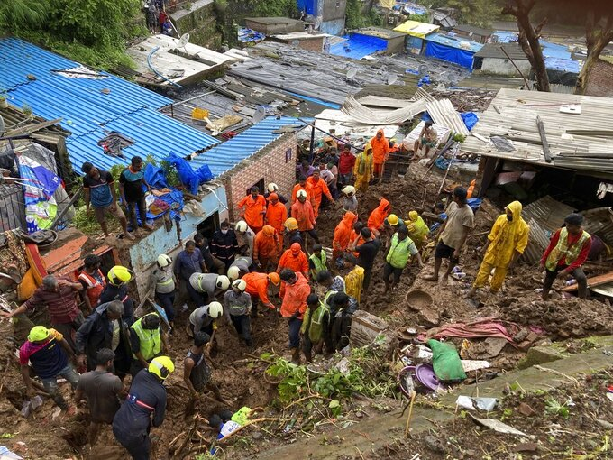 Rescuers look for survivors after a wall collapsed on several slum houses heavy monsoon rains in the Mahul area of Mumbai, India, Sunday, July 18, 2021. More than a dozen people were killed in the incident. (AP Photo/Rajanish Kakade)