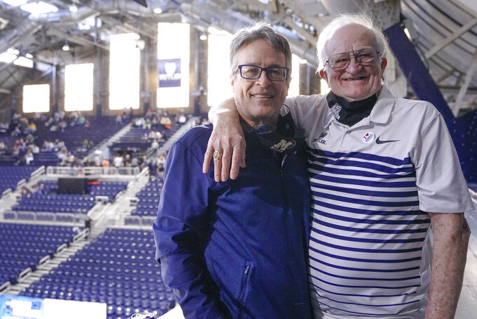 "Bobby Plump, right, star of the 1954 Milan state championship basketball team that inspired the movie ""Hoosiers,"" poses for a portrait with the movie's writer, Angelo Pizzo, at Hinkle Fieldhouse in Indianapolis, during a Sweet 16 NCAA men's basketball game Saturday, March 27, 2021. Most fans naturally link Plump with Hinkle Fieldhouse because of the last-second shot he made in 1954 to give Milan High School the state championship. They know it as the shot that inspired the movie ""Hoosiers."" Around the state, Plump is revered for other reasons. (AP Photo/AJ Mast)"