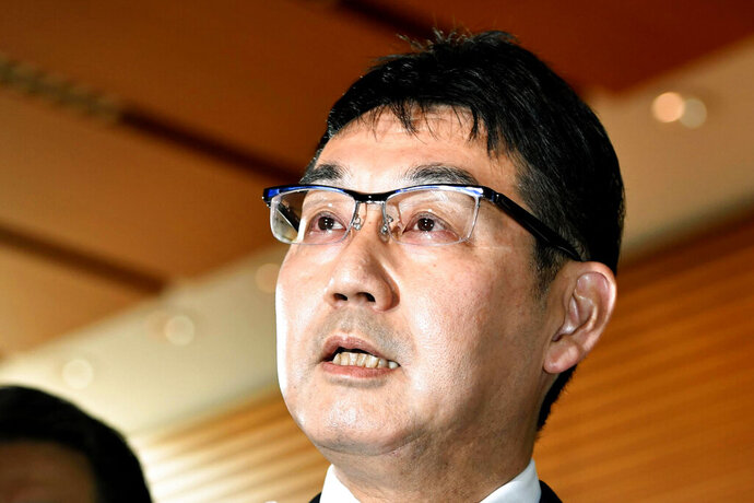 Japanese Justice Minister Katsuyuki Kawai speaks to reporters after submitting his resignation to Prime Minister Shinzo Abe at Abe's official residence in Tokyo Thursday, Oct. 31, 2019.  Kawai resigned over election fraud allegations involving his wife, also a lawmaker, and about his own gift-giving allegations reported in a tabloid magazine. (Yoshitaka Sugawara/Kyodo News via AP)