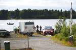 Emergency services attend the accident site at a small harbor at Ume river, outside Umea, Sweden, Sunday July 14, 2019. Swedish officials say a small plane carrying parachutists crashed in northern Sweden and all nine of the people on board were killed. (Samuel Pettersson/TT via AP)