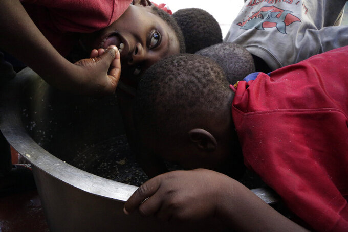 FILE - In this Friday, March 22, 2019 file photo, children scrape through for remaining rice inside a pot at a center for those displaced after Cyclone Idai hit coastal Mozambique, in Beira, Mozambique. The U.N. high commissioner for refugees, Filippo Grandi said Friday June 17, 2021, that conflicts and the impact of climate change in places like Mozambique were among the leading sources of new flows of refugees and internally displaced people in 2020.(AP Photo/Themba Hadebe, File)