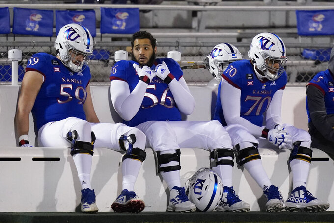 Kansas offensive linemen Jack Murphy (59), Ronaldo Sigers (56) and Nick Williams (70) sit on the bench during the second half of the team's NCAA college football game against TCU in Lawrence, Kan., Saturday, Nov. 28, 2020. TCU won 59-23. (AP Photo/Orlin Wagner)