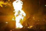Fires burn as police storm part of the Hong Kong Polytechnic University campus during the early morning hours in Hong Kong, Monday, Nov. 18, 2019. Police breached the university campus held by protesters early Monday after an all-night siege that included firing repeated barrages of tear gas and water cannons. (AP Photo/Ng Han Guan)