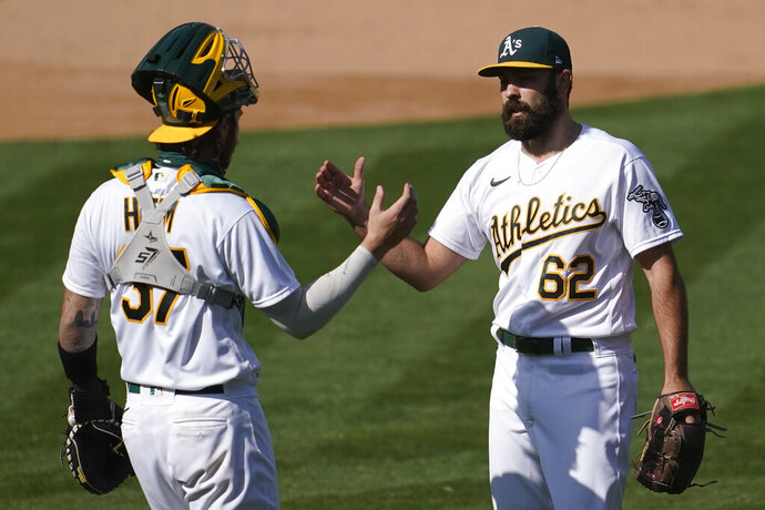 Oakland Athletics catcher Jonah Heim, left, celebrates with Lou Trivino after the Athletics defeated the San Francisco Giants in a baseball game in Oakland, Calif., Saturday, Sept. 19, 2020. (AP Photo/Jeff Chiu)