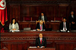 Tunisian designated Prime Minister Habib Jemli, below center, delivers his speech at the parliament, Friday Jan. 10, 2020. Tunisia's parliament is expected to hold a confidence vote Friday on designated prime minister Habib Jemli's government. (AP Photo/Hassene Dridi)