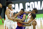 Abilene Christian's Joe Pleasant, center, battles for the ball with Texas' Jericho Sims, left, and Texas' Greg Brown (4) during the first half of a college basketball game in the first round of the NCAA tournament at Lucas Oil Stadium in Indianapolis Saturday, March 20, 2021. (AP Photo/Mark Humphrey)