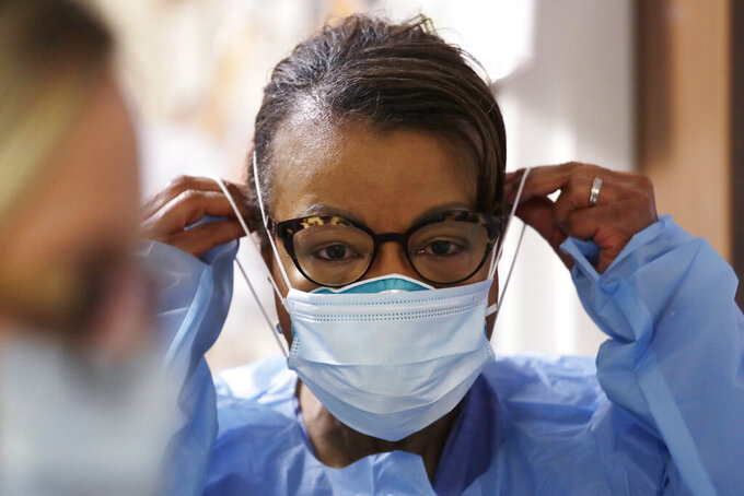 FILE - In this Friday, May 8, 2020 file photo, a respiratory therapist pulls on a second mask over her N95 mask before adding a face shield as she gets ready to go into a patient's room in the COVID-19 Intensive Care Unit at a hospital in Seattle.  Medical providers may soon return to using one medical N95 mask per patient, a practice that was suspended during the pandemic due to deadly supply shortages. (AP Photo/Elaine Thompson)