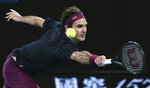 Switzerland's Roger Federer makes a backhand return to Serbia's Filip Krajinovic during their second round singles match at the Australian Open tennis championship in Melbourne, Australia, Wednesday, Jan. 22, 2020. (AP Photo/Dita Alangkara)