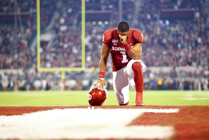 Oklahoma Sooners quarterback Jalen Hurts (1) prays in the end zone before the NCAA football game between the against the Iowa State Cyclones and the Oklahoma Sooners at Gaylord Family-Oklahoma Memorial Stadium in Norman, Okla., on Saturday, Nov. 9, 2019. (Ian Maule/Tulsa World via AP)