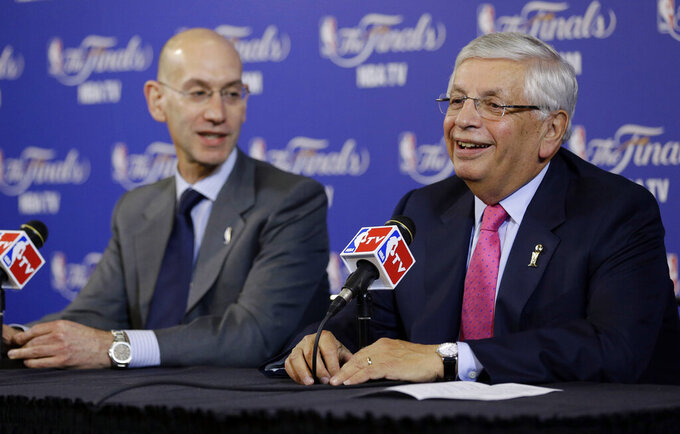 FILE - In this Thursday, June 6, 2013 file photo, David Stern, NBA Commissioner, right, and Adam Silver, Deputy Commissioner, speak before the start of Game 1 of the NBA Finals basketball game between the San Antonio Spurs and Miami Heat in Miami. David Stern, who spent 30 years as the NBA's longest-serving commissioner and oversaw its growth into a global power, has died on New Year's Day, Wednesday, Jan. 1, 2020. He was 77. (AP Photo/Wilfredo Lee, File)