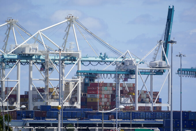 In this April 9, 2021 photo, cargo containers are shown stacked near cranes at PortMiami in Miami. The U.S. trade deficit increased, Thursday, Aug. 5,, to a record $75.7 billion in June as a rebounding American economy sent demand for imports surging.   (AP Photo/Wilfredo Lee)