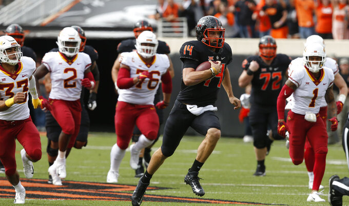 Oklahoma State quarterback Taylor Cornelius (14) rushes for 48 yards against Iowa State in the first half of an NCAA college football game in Stillwater, Okla., Saturday, Oct. 6, 2018. (AP Photo/Sue Ogrocki)