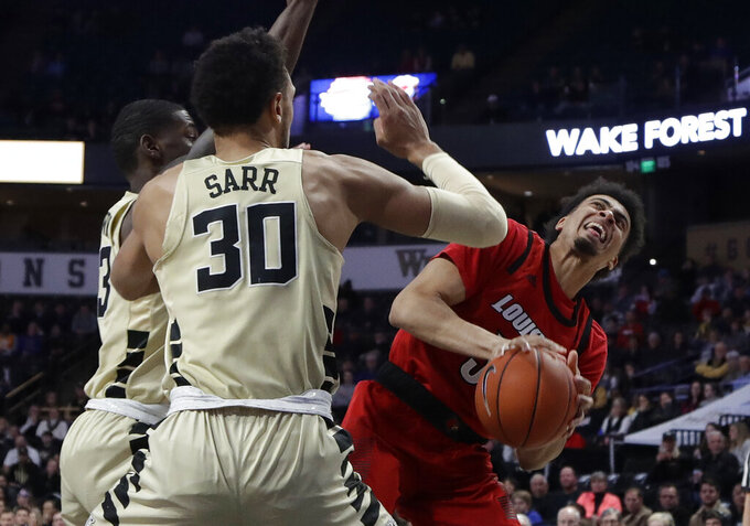 Louisville's Malik Williams (5) looks to shoot against Wake Forest's Olivier Sarr (30) during the first half of an NCAA college basketball game in Winston-Salem, N.C., Wednesday, Jan. 30, 2019. (AP Photo/Chuck Burton)