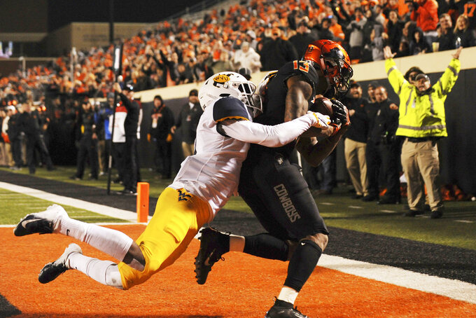 Oklahoma State wide receiver Tyron Johnson, right, catches a touchdown pass while under pressure from West Virginia cornerback Josh Norwood during the second half of an NCAA college football game in Stillwater, Okla., Saturday, Nov. 17, 2018. Oklahoma State upset West Virginia 45-41.(AP Photo/Brody Schmidt)