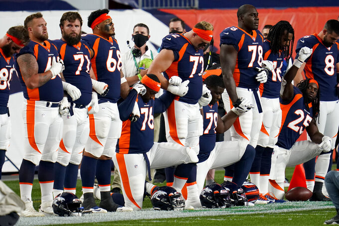 Members of the Denver Broncos stand and kneel during the national anthem prior to an NFL football game against the Tennessee Titans, Monday, Sept. 14, 2020, in Denver. (AP Photo/David Zalubowski)