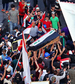 In this Thursday, Oct. 31, 2019 photo, mourners and protesters carry the flag-draped coffin of Mohammed Sadiq during his funeral during a demonstration at Tahrir Square in Baghdad, Iraq. Sadiq was killed while participating in the anti-government ongoing protests, his family said. (AP Photo/Hadi Mizban)